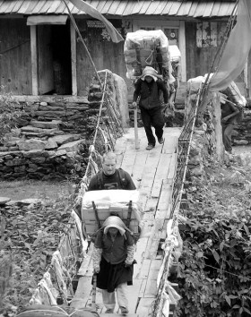 Crossing a foot bridge between Sherpa porters on the way to Everest Base Camp, Nepal 2007
